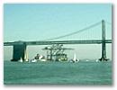 Shipping cranes sail under Bay Bridge